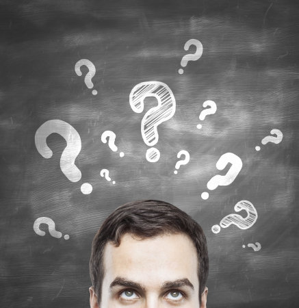 intelligent solutions: man with questions symbol on blackboard Stock Photo