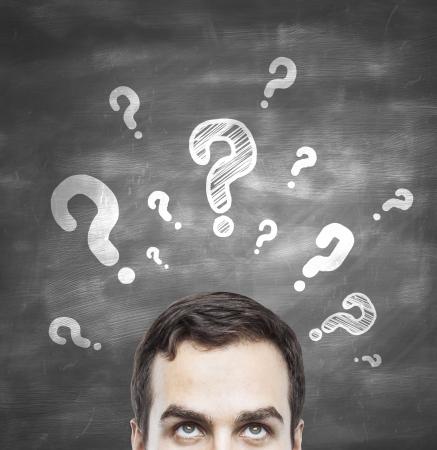lavagna: uomo con domande simbolo sulla lavagna