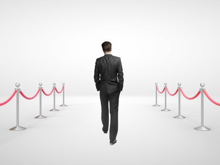businessman walking and stanchions barrier in white room photo