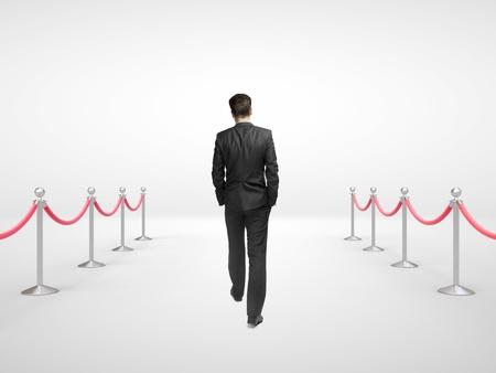 acomodador: empresario caminando y barrera puntales en la habitaci�n blanca