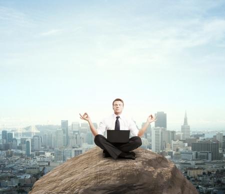 meditation stones: businessman sitting with laptop on mountain