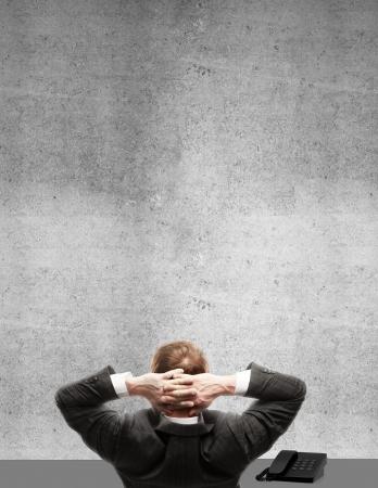 pensamiento creativo: el hombre sentado en la oficina y mirando a la pared