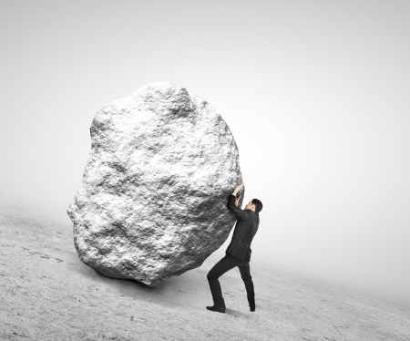 push up: businessman holding rock on white backround Stock Photo