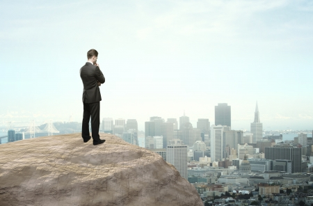 future city: businessman thinking and looking at city in distance