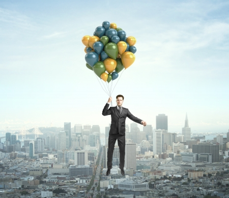 businessman flying with air baloons over the city photo