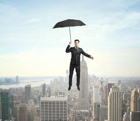 businessman flying with umbrella over the city photo