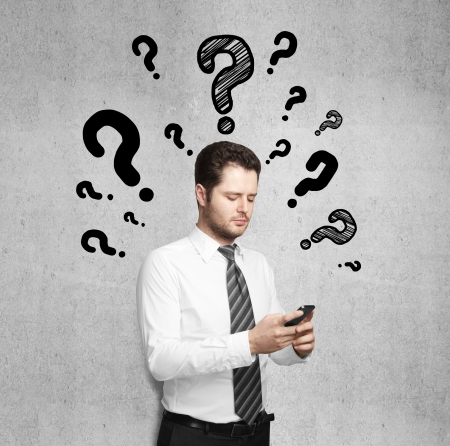 businessman holding phone with drawing question marks photo