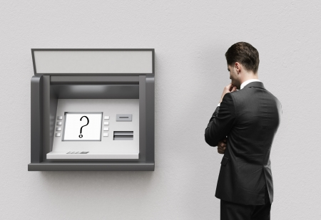 cash dispenser: businessman thinking and looking at atm Stock Photo