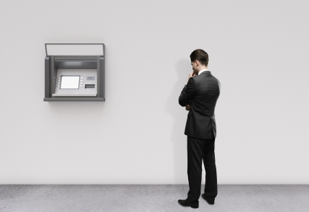 man thinking and looking at atm photo