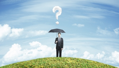 businessman standing with umbrella on field photo