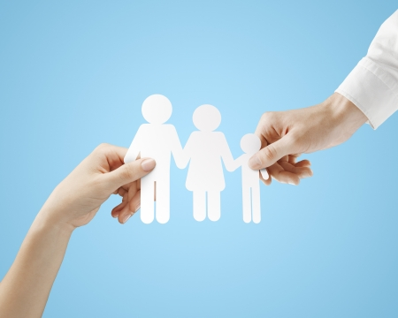 linked hands: hands holding paper family  on a blue background