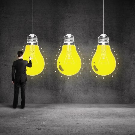 businessman drawing glowing bulb on wall Stock Photo - 19667137
