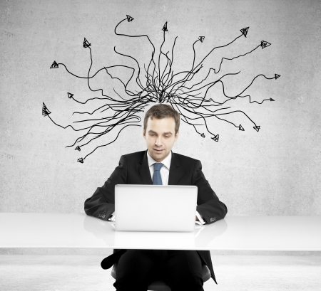 Businessman with laptop and arrows over head photo