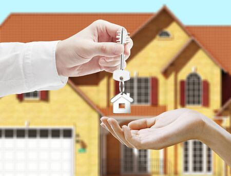 thumb keys: hand holding key and blured house on background Stock Photo
