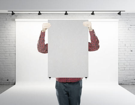man holding poster with pin on loft studio photo