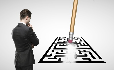 clear strategy: businessman looking at pencil with eraser erases maze