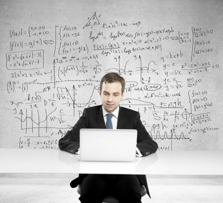 businessman sitting at a table with laptop and formula on background photo
