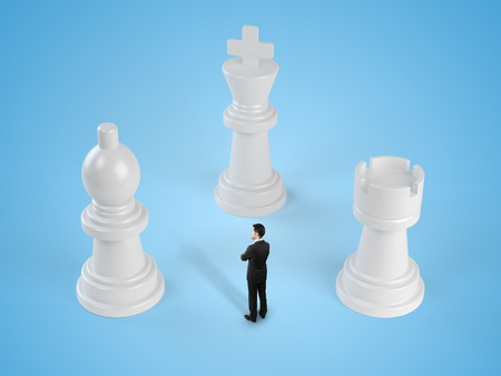 businessman standing among chess pieces isolated in blue photo