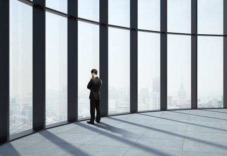 businessman standing near office window photo