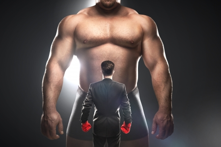 human fist: man boxing against a big muscular man