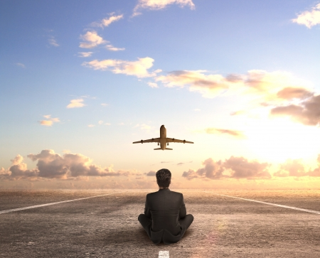 businessman sitting on runway and looking on  airplane photo