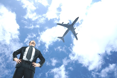 businessman looking on airplane in blue sky photo