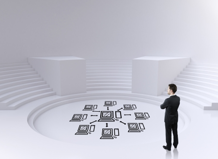 man thinking in big circle room and drawing computer network on floor photo