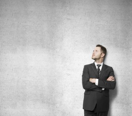 hombre pensando: hombre de negocios apoyado contra un muro de hormig�n y el pensamiento Foto de archivo