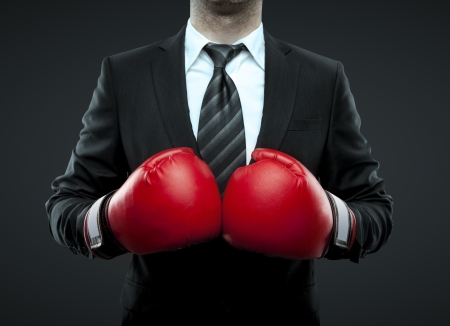 business protection: businessman in boxing gloves isolated on black Stock Photo