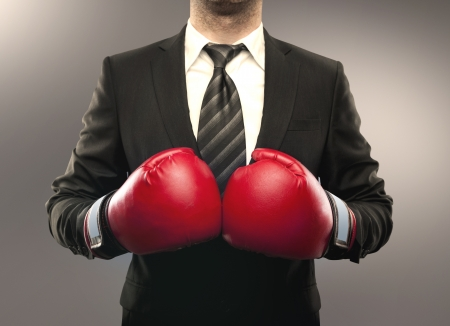 protective suit: businessman in boxing gloves isolated on gray