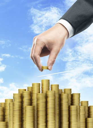 Hand put coins to money staircase and blue sky photo