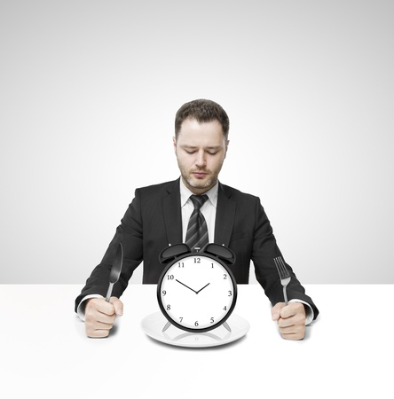 businessman sitting on table and eating clock photo