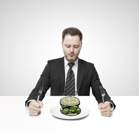 businessman sitting on table and eating hamburger money photo
