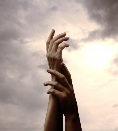 hands and cloudy sky on background photo