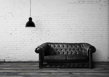old sofa: brick room with leather sofa Stock Photo