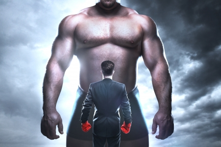 business disagreement: businessman boxing against a big muscular man Stock Photo