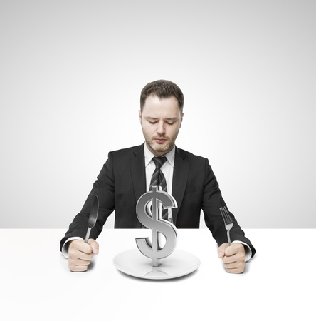 lunch meeting: businessman sitting on table and eating money symbol