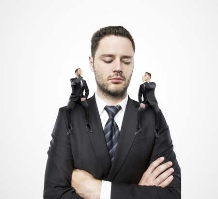 on shoulders of a businessman siting two little man, and whispers in my ear Stock Photo - 20339994