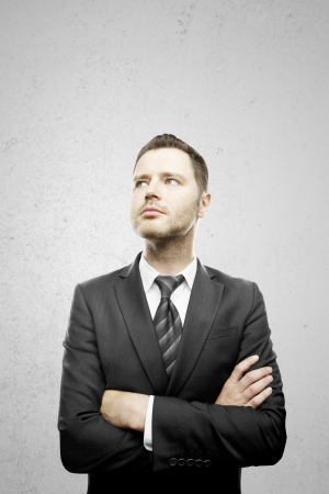young: businessman standing and folded his hands on gray background
