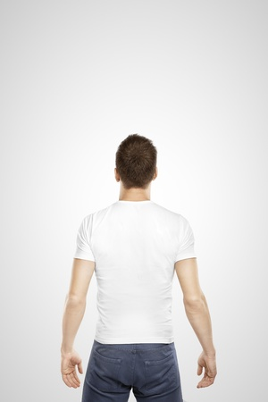 standing man: young man standing back on a white background