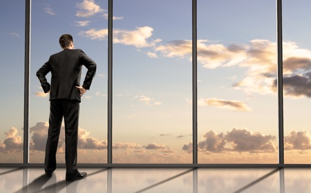 businessman standing in office and looking in sky photo