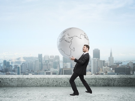 businessman holding globe on city background photo
