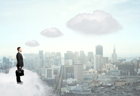 businessman standing on cloud and looking at city photo