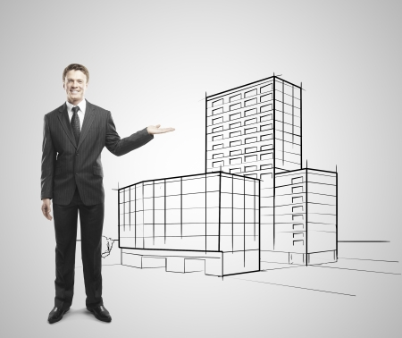 businessman holding drawing skyscraper on a white background photo
