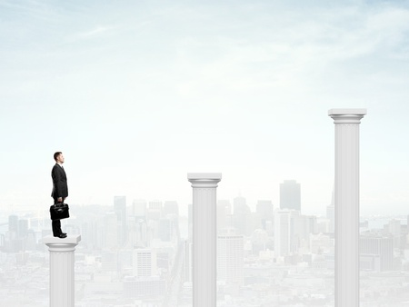 businessman with briefcase standing on a column photo