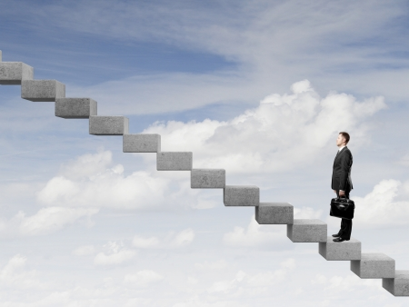 difficult journey: Businessman stepping up a staircase and sky
