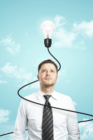businessman and lamp with cable on sky background photo