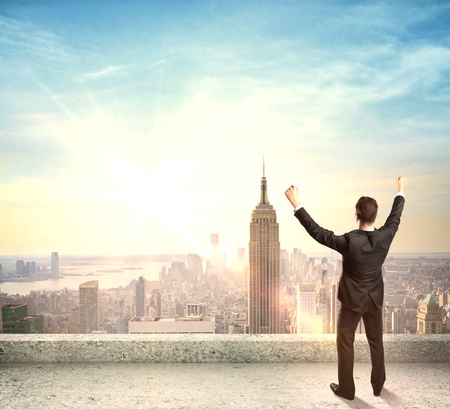 happines: happy businessman standing on roof and city on back