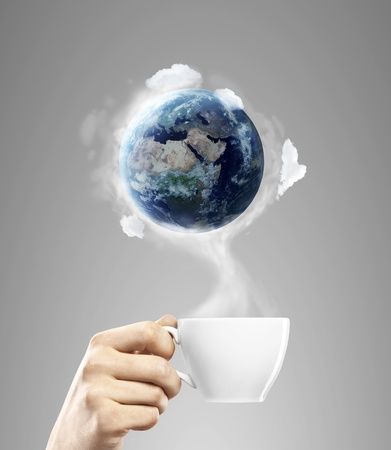 tasse de caf� � la main avec de la terre photo