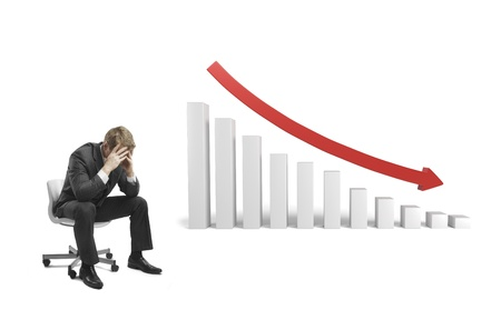 and decline: sad businessman sitting on chair with falling 3d graph Stock Photo